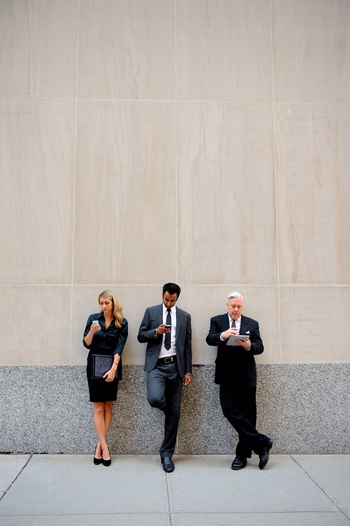 Stock Photo: 1439R-1147679 Three businesspeople leaning on a wall, looking at phones and digital tablets