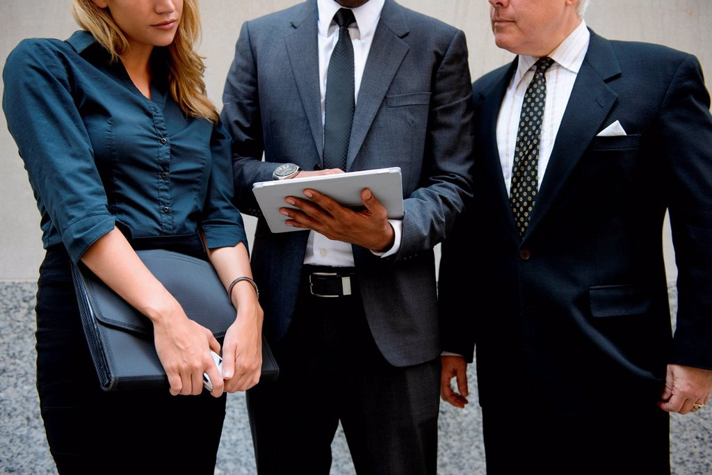 Three businesspeople looking at a digital tablet : Stock Photo