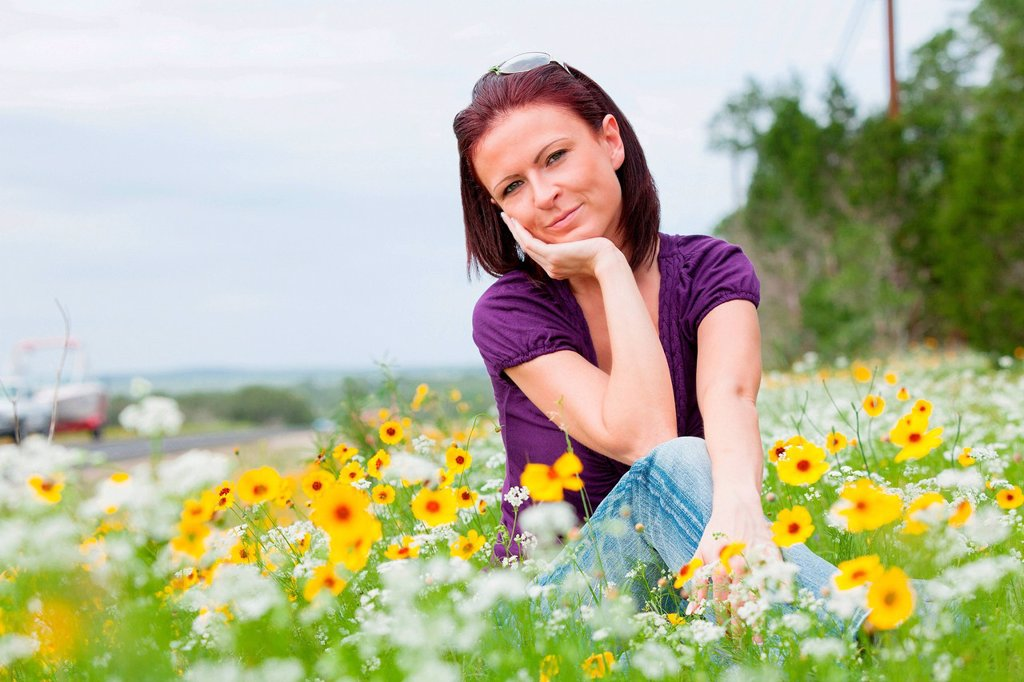 Stock Photo: 1439R-1147683 Mid adult woman sitting in a field of flowers