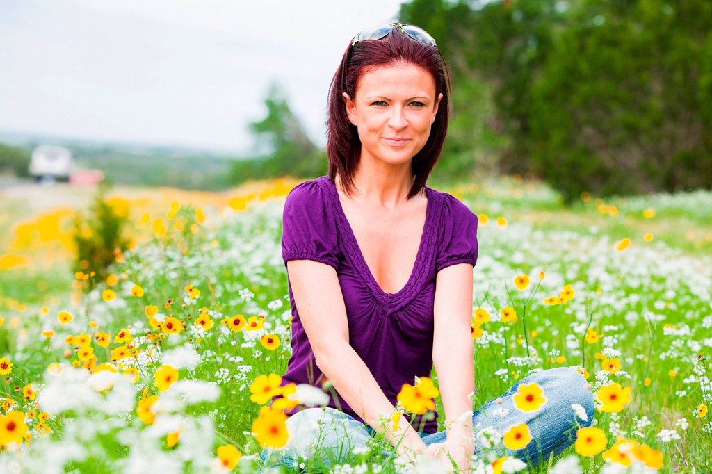 Stock Photo: 1439R-1147684 Mid adult woman sitting in a field of flowers