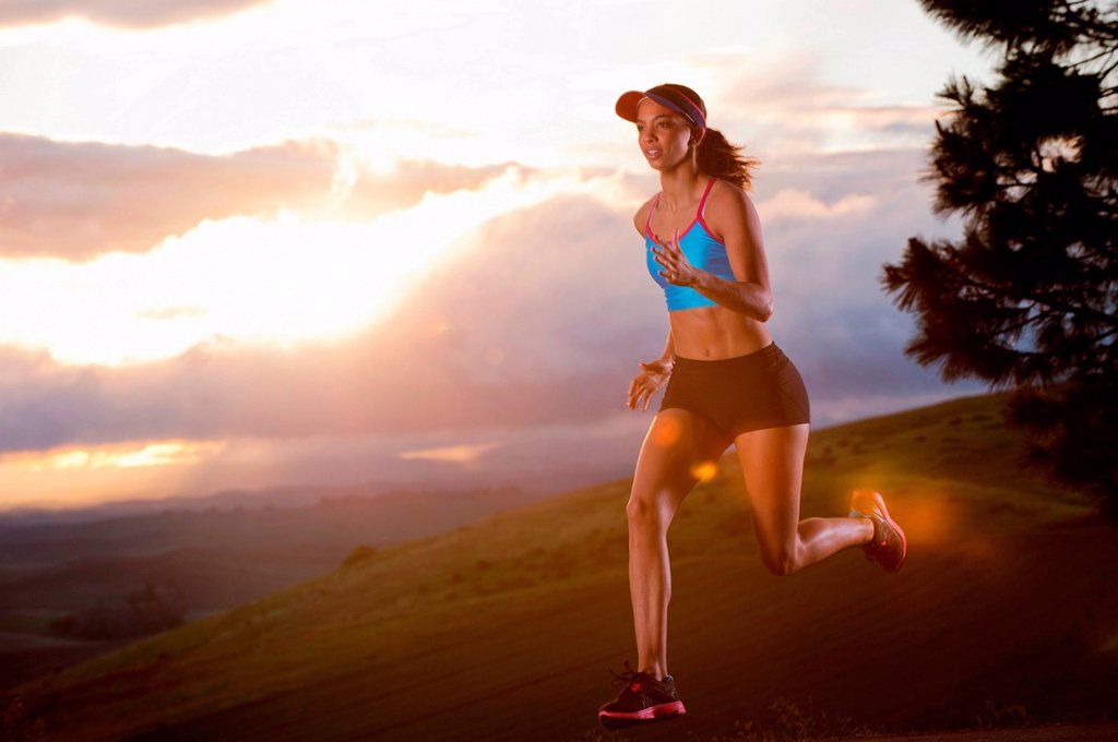 Young woman running in rural setting at sunrise : Stock Photo