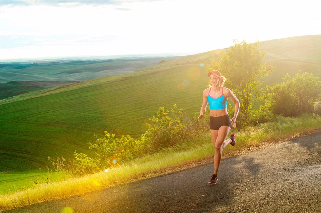 Stock Photo: 1439R-1147702 Young woman running in landscape of Palouse Hills, Washington, USA