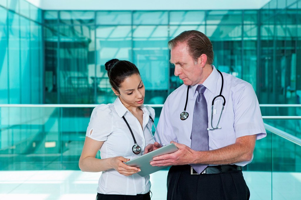 Doctors discussing medical records on digital tablet : Stock Photo