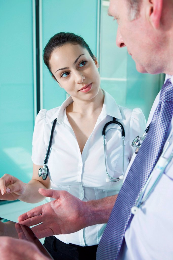 Stock Photo: 1439R-1147712 Doctors discussing medical records on digital tablet