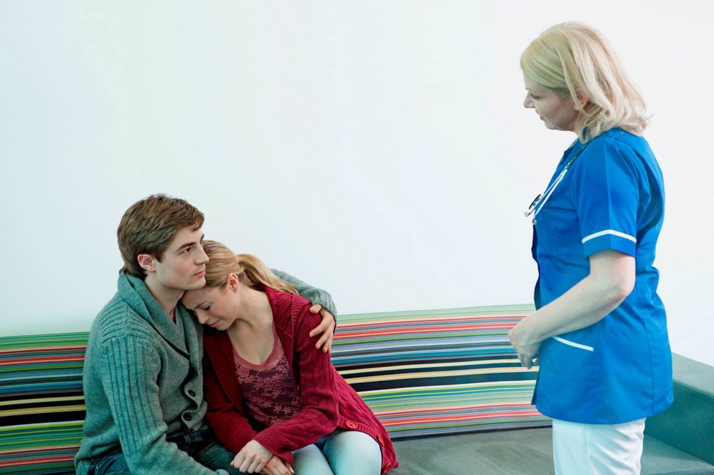 Stock Photo: 1439R-1147720 Young couple with nurse in hospital waiting room