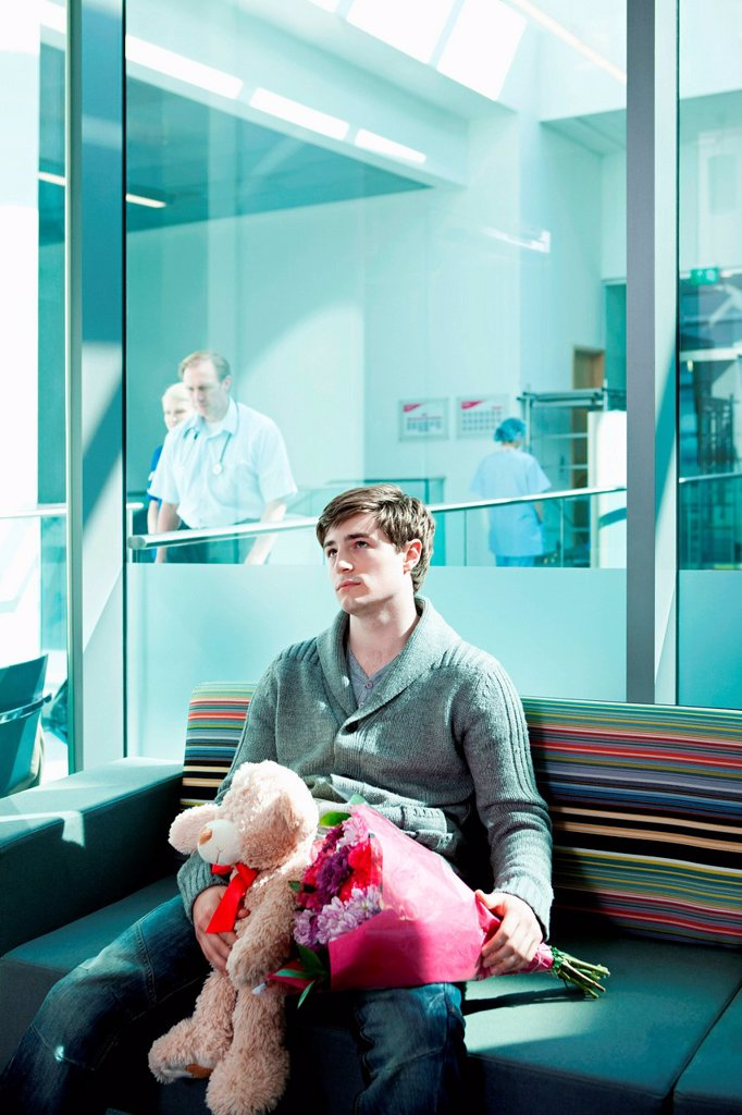 Stock Photo: 1439R-1147721 Man in hospital waiting room with bouquet and teddy bear