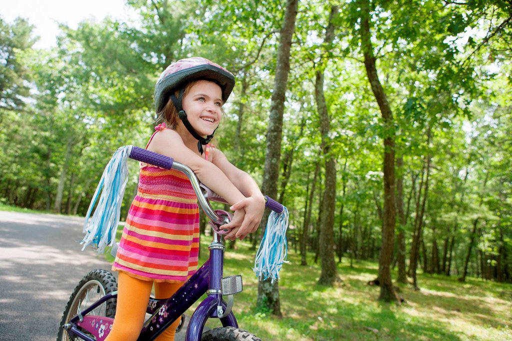 Stock Photo: 1439R-1147730 Girl leaning on bicycle handlebars