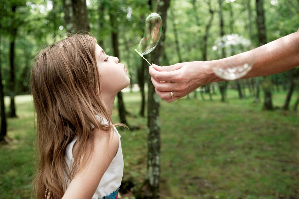 Stock Photo: 1439R-1147738 Woman holding bubble wand, girl blowing bubble