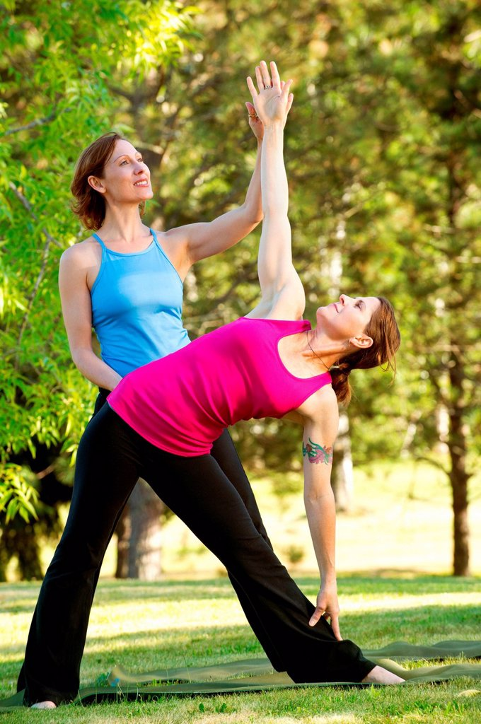 Yoga instructor and student in park : Stock Photo