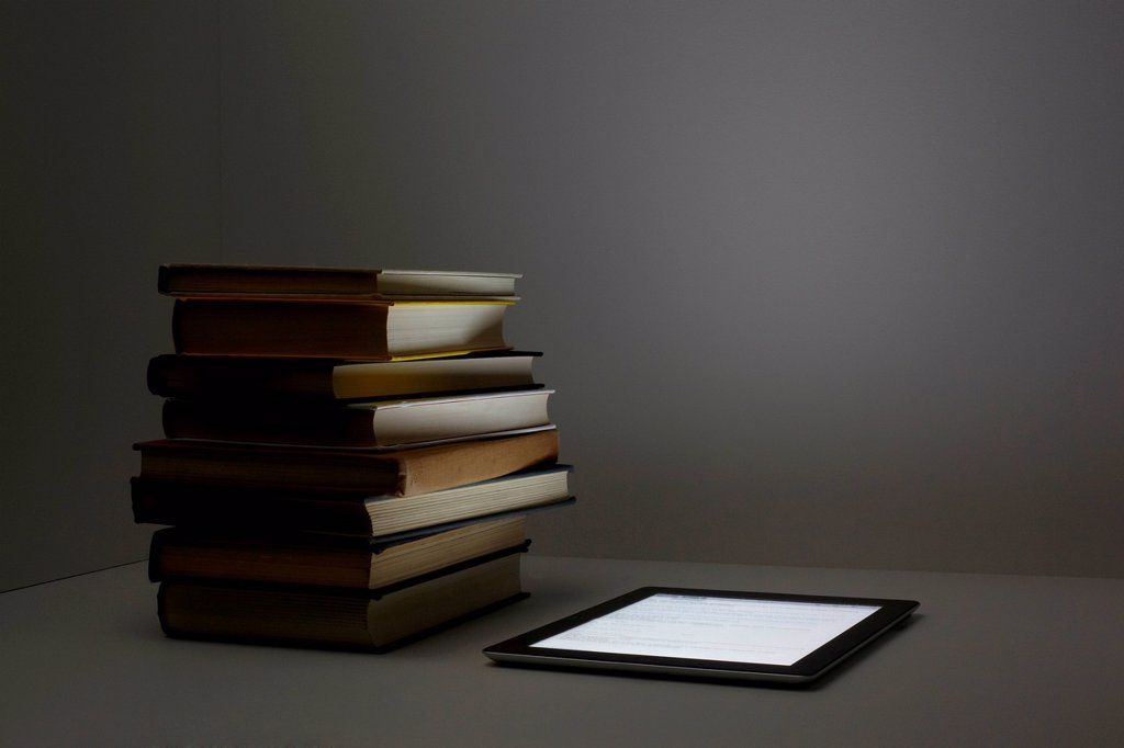 Stock Photo: 1439R-1147788 Stack of books with digital tablet