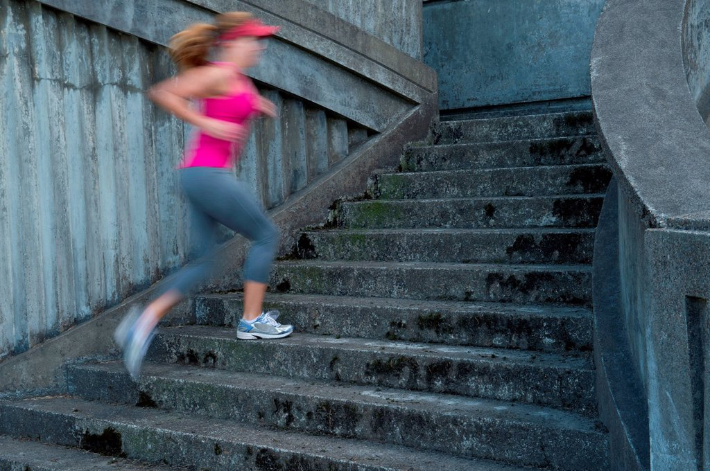 Stock Photo: 1439R-1147792 Young woman running up stairs, motion blur