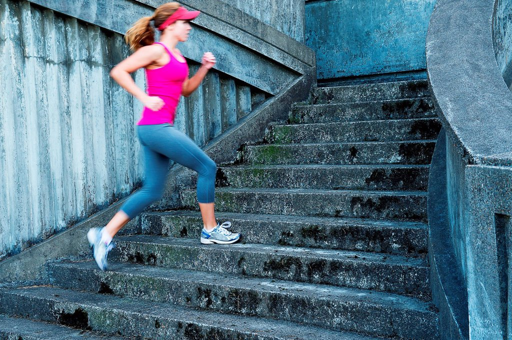 Young woman running up stairs : Stock Photo