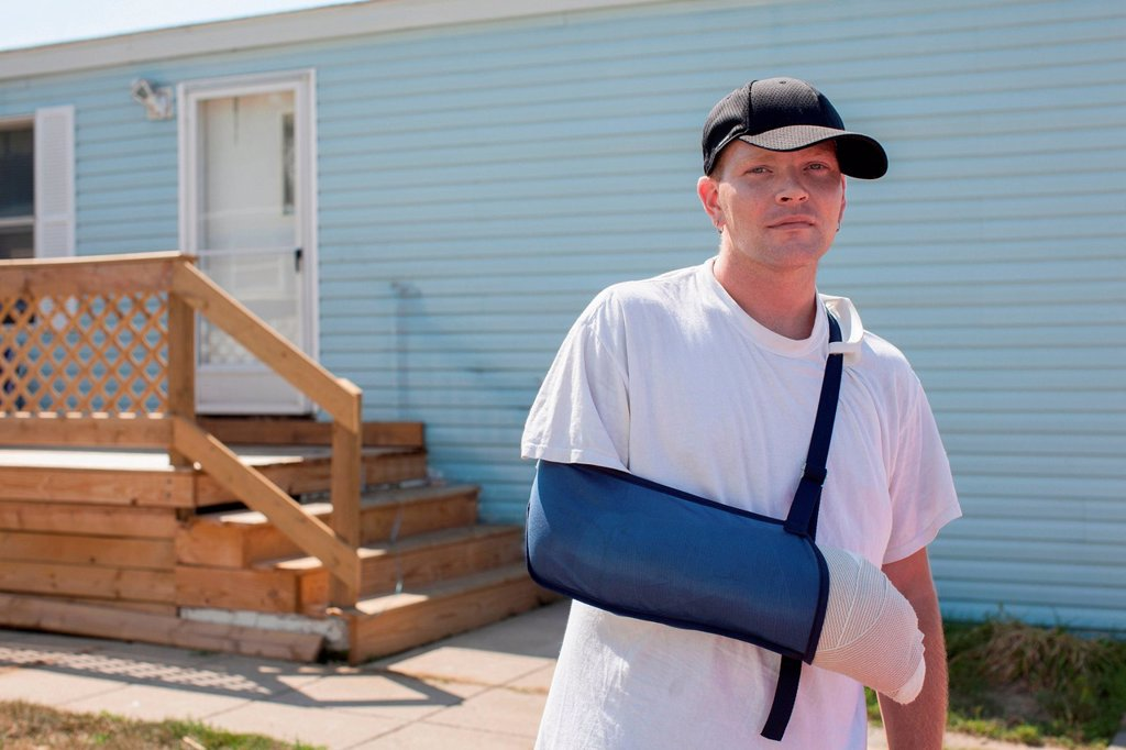 Stock Photo: 1439R-1147802 Man outside house with arm in sling