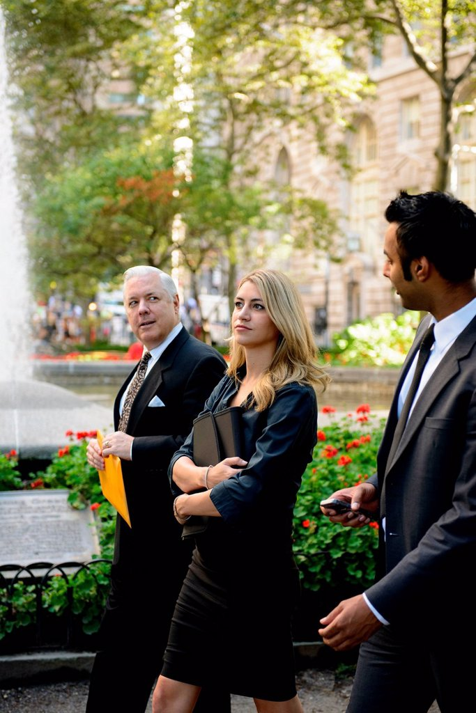 Stock Photo: 1439R-1147823 Businesspeople walking through financial district park