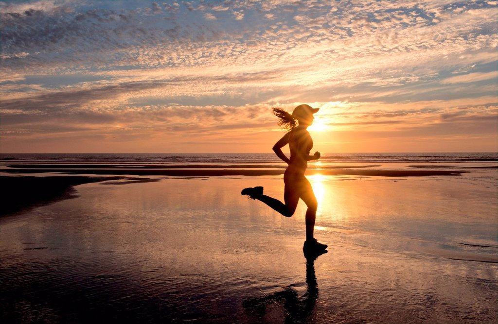 Stock Photo: 1439R-1147833 Woman running on beach at sunrise