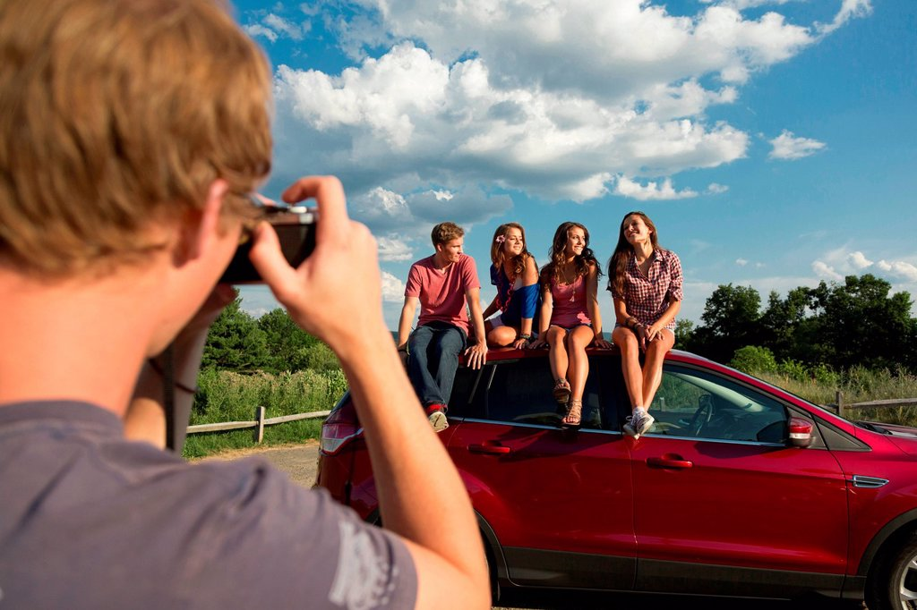 Friends sitting on car roof, young man taking photograph : Stock Photo