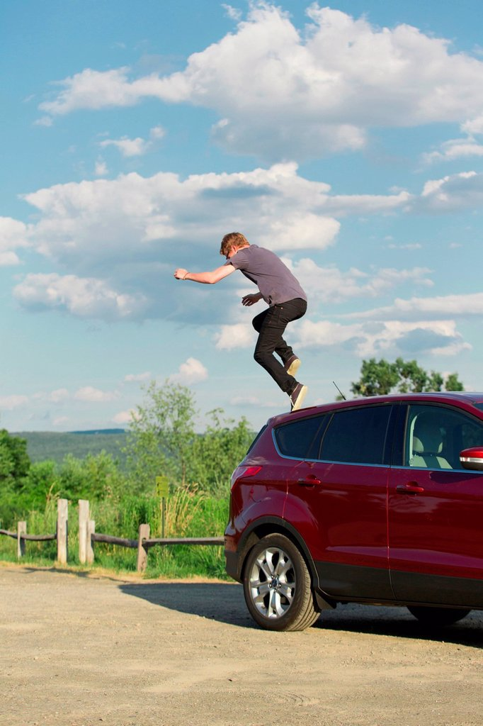 Young man jumping off car : Stock Photo