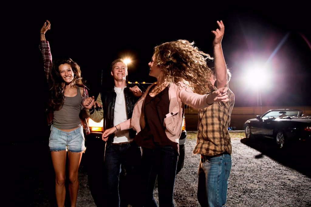 Four friends in parking lot at night : Stock Photo