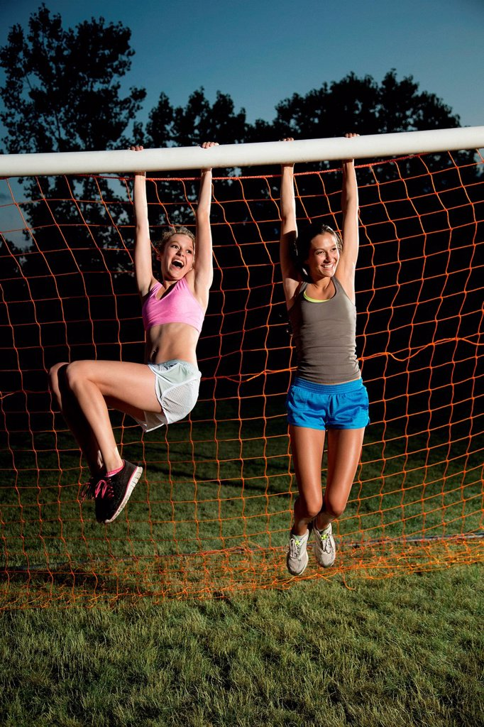 Girls hanging from soccer goal : Stock Photo