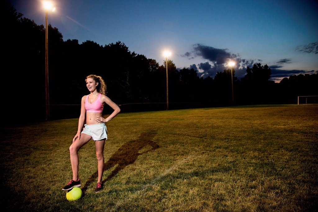 Stock Photo: 1439R-1147913 Girl on soccer pitch at night