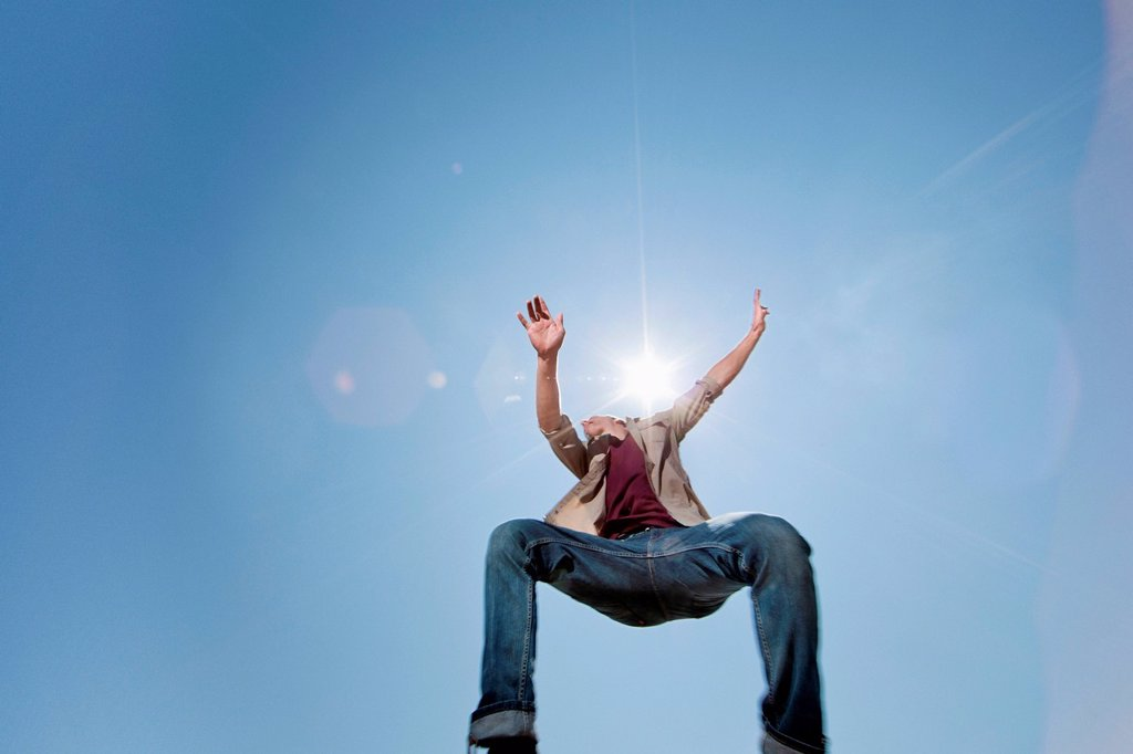 Stock Photo: 1439R-1147944 Young man jumping against blue sky, low angle