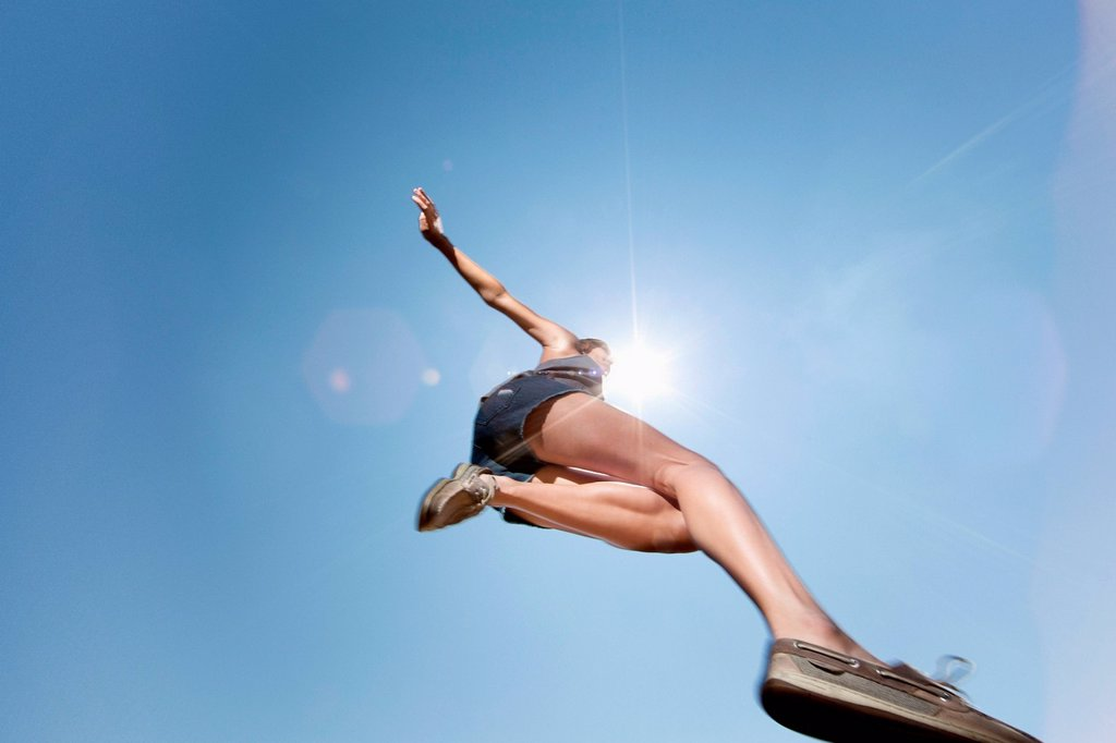 Stock Photo: 1439R-1147945 Girl jumping against blue sky, low angle