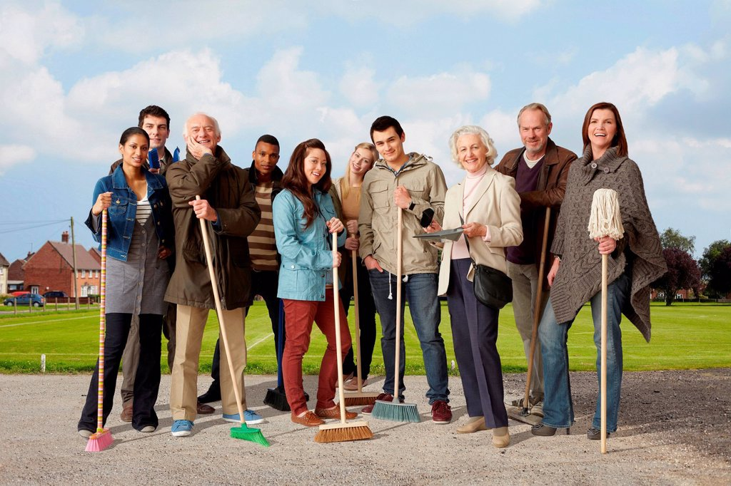 Group of people standing with brooms and mop : Stock Photo