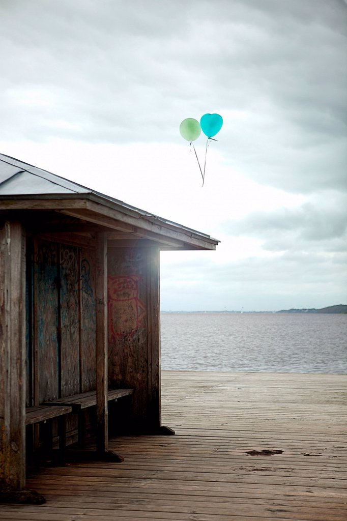 Balloons floating by old seaside shelter, Flensburg, Germany : Stock Photo