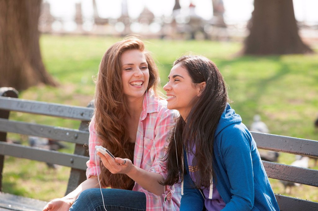 Stock Photo: 1439R-1148084 Young women sharing music in the park