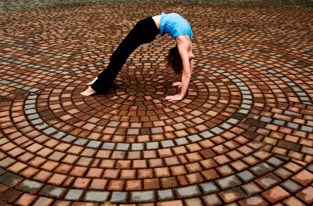 Woman bending backwards in paving stone circles : Stock Photo