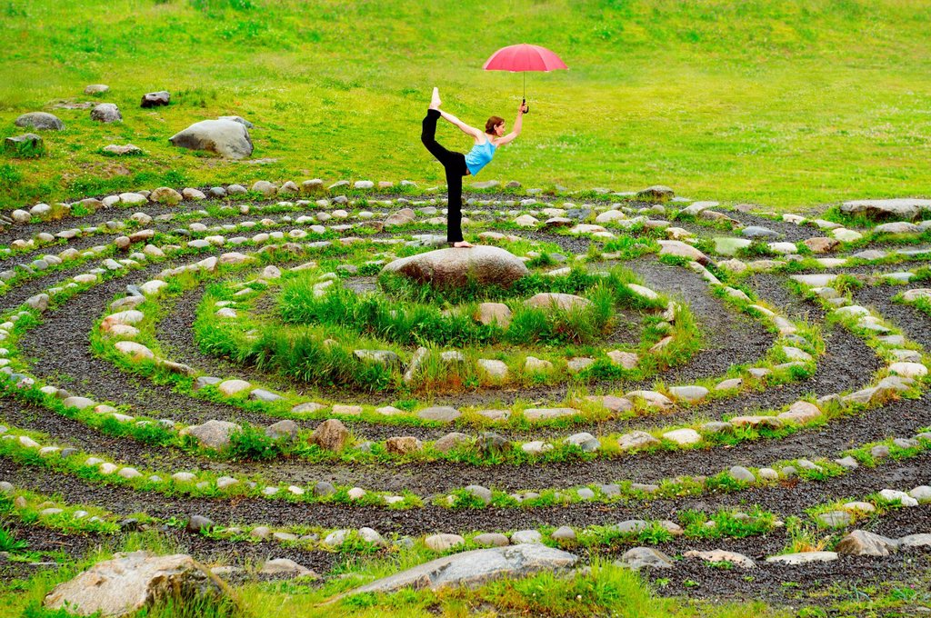 Stock Photo: 1439R-1148134 Woman holding an umbrella whilst in yoga pose in centre of stone maze