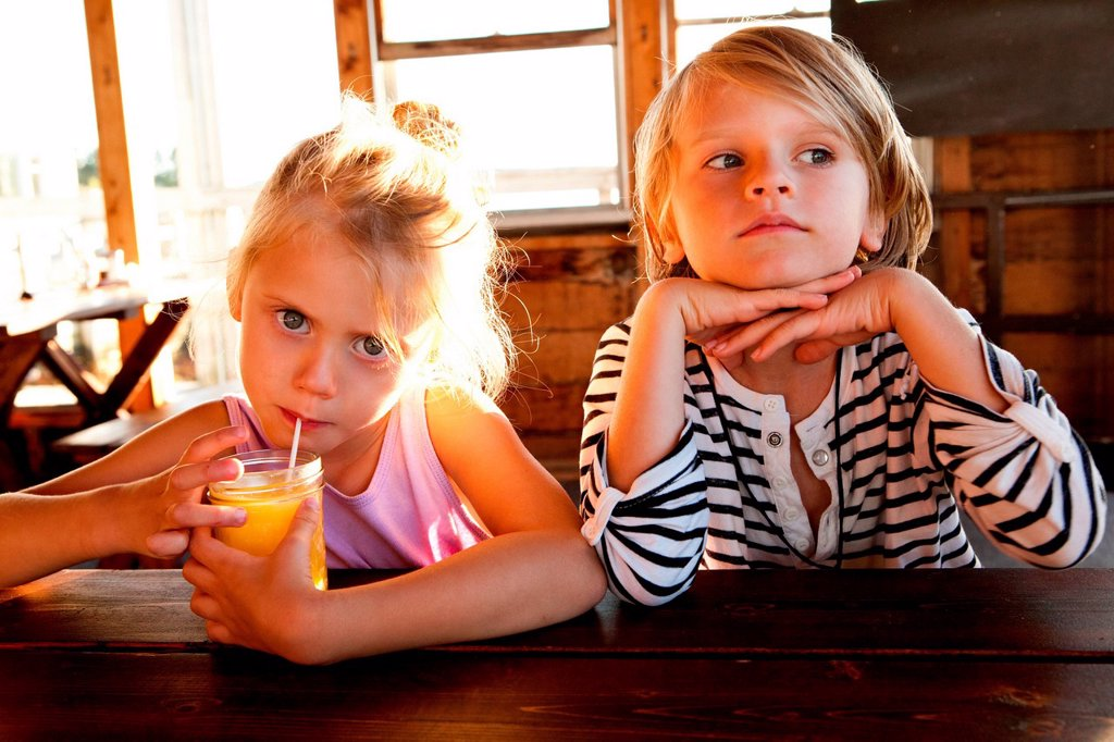 Girl drinking juice and boy looking thoughtful : Stock Photo
