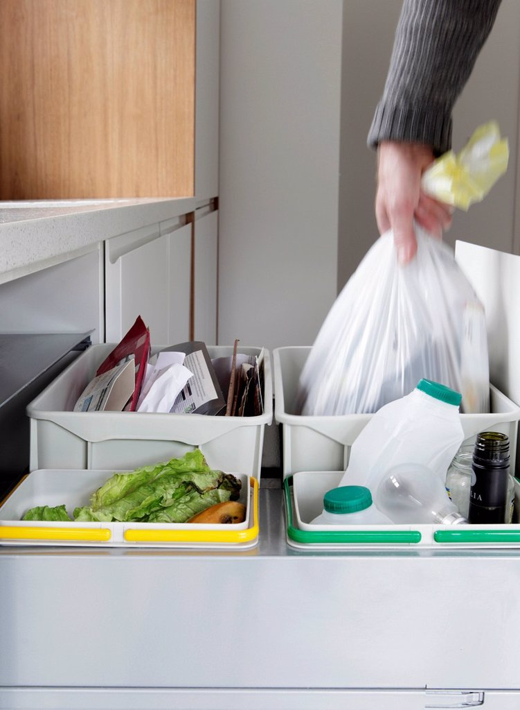 Stock Photo: 1439R-1148324 Person removing rubbish bag from waste and recycling drawer