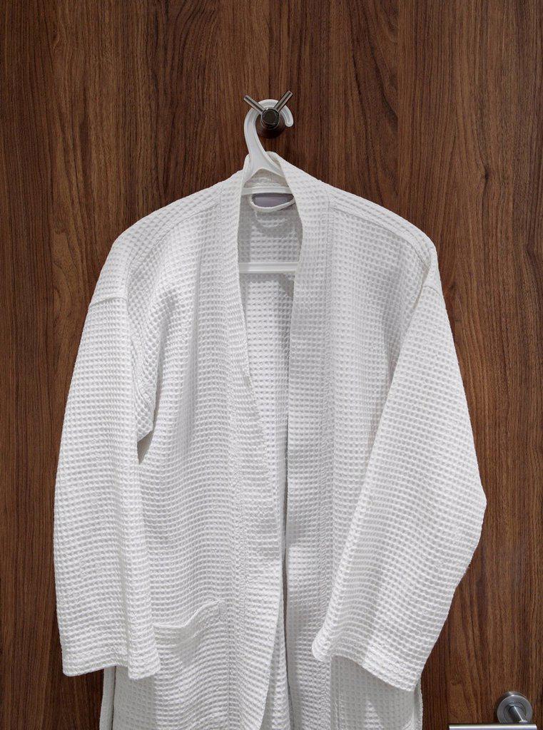 Stock Photo: 1439R-1148326 White bathrobe hanging on door