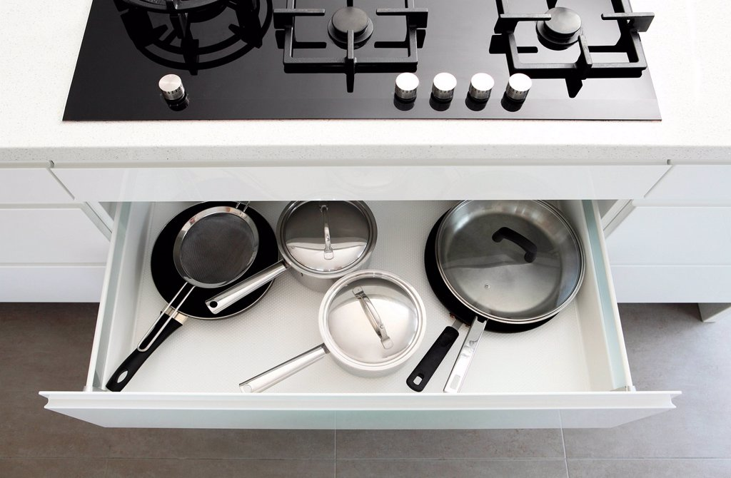 Stock Photo: 1439R-1148336 Saucepans in draw under hob