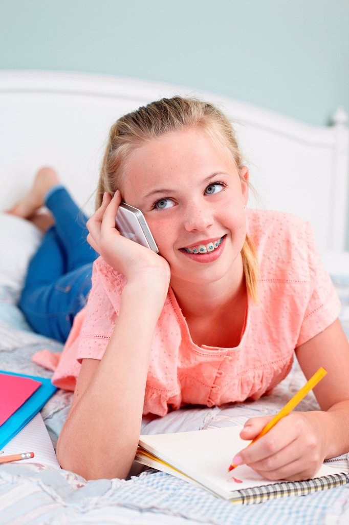 Stock Photo: 1439R-1148368 Teenage girl on cellphone with notepad