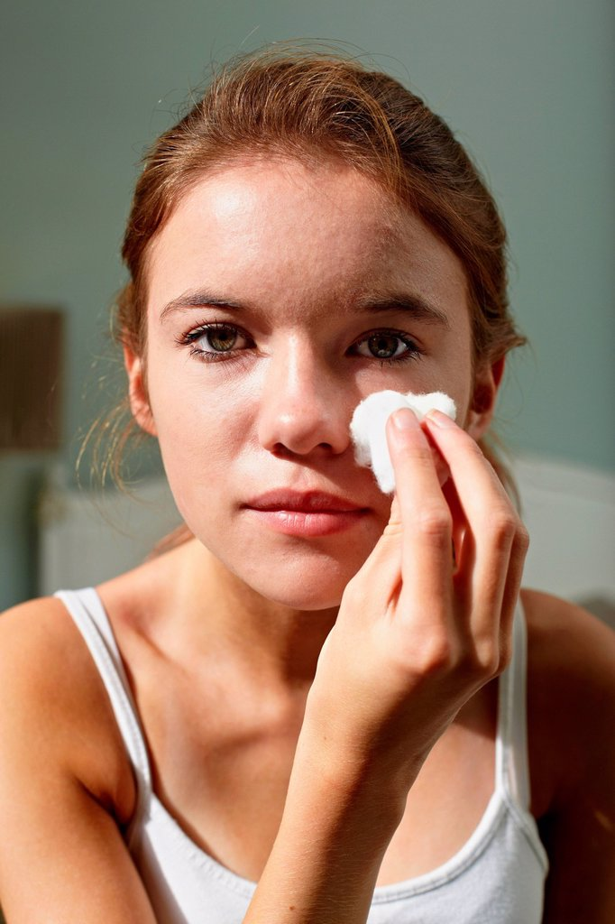 Stock Photo: 1439R-1148369 Teenage girl cleansing her face