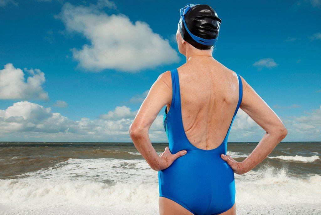 Senior woman wearing swimsuit looking towards sea : Stock Photo