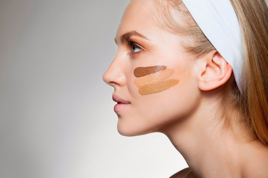 Woman with stripes of foundation on cheek : Stock Photo