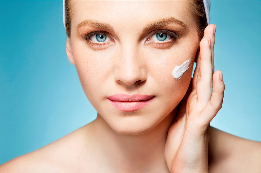 Stock Photo: 1439R-1148551 Woman applying moisturiser