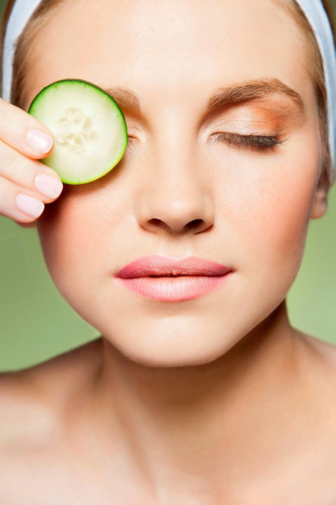 Woman covering eye with piece of cucumber : Stock Photo