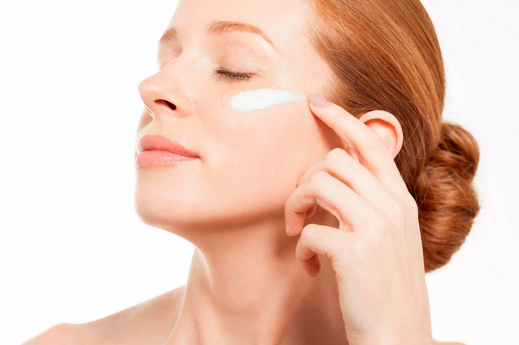 Stock Photo: 1439R-1148587 Woman applying moisturiser with eyes closed