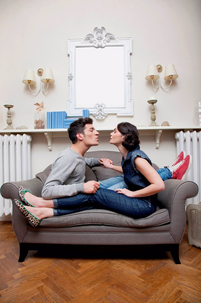 Stock Photo: 1439R-1148618 Couple on sofa kissing