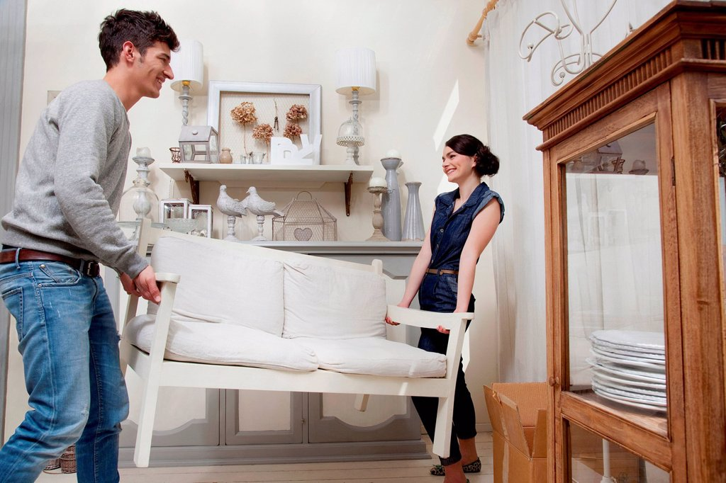 Stock Photo: 1439R-1148620 Couple moving sofa