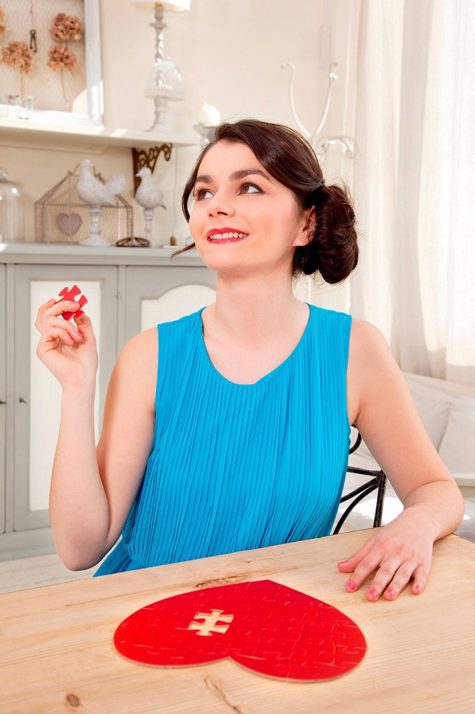 Stock Photo: 1439R-1148636 Woman doing heart shaped jigsaw puzzle holding piece