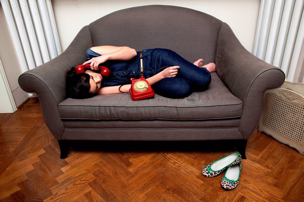 Woman lying on sofa on the telephone : Stock Photo