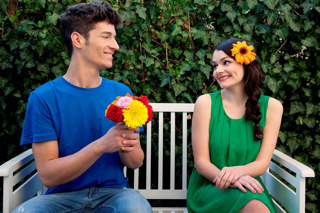 Stock Photo: 1439R-1148654 Couple on bench, man holding flowers