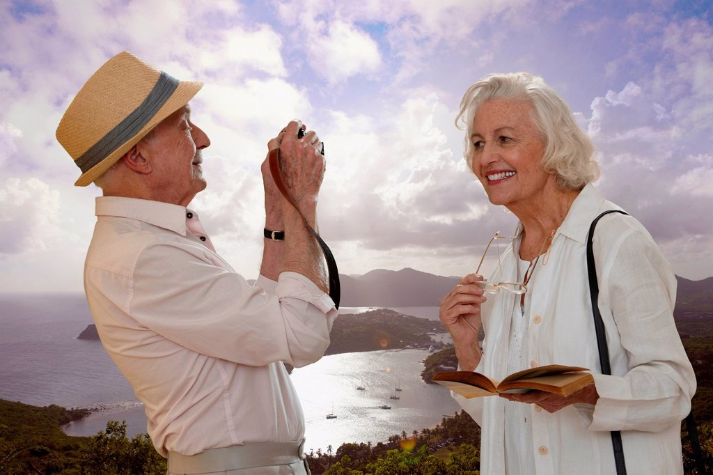 Senior man photographing wife by the sea : Stock Photo