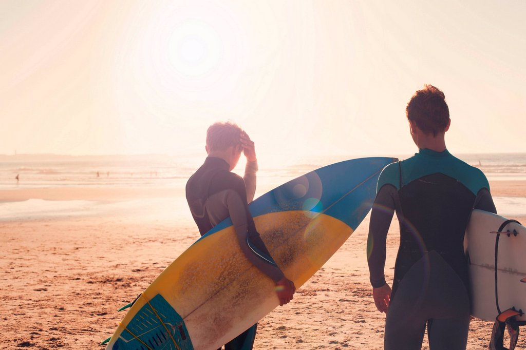 Surfers looking out towards sea : Stock Photo