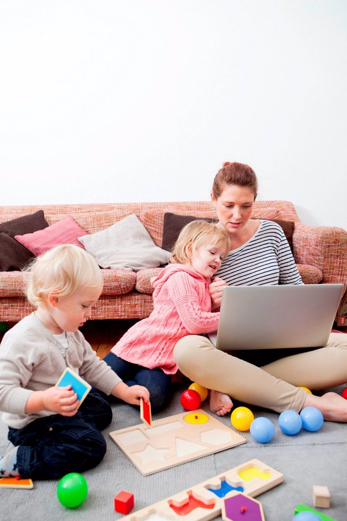 Mother using laptop, children playing : Stock Photo